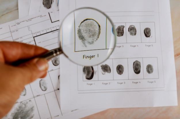 Kriminelle fingerabdruckkarte und vergrößerungsglas kriminalpolizei