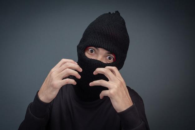 Kriminelle tragen eine maske in schwarz auf grau
