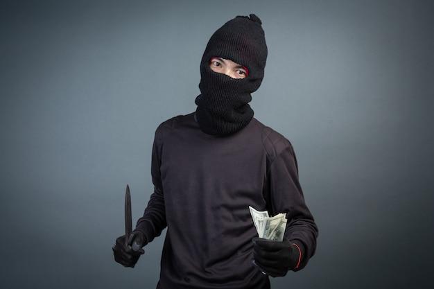 Kriminelle tragen eine schwarze maske und halten sich dunkel an grau