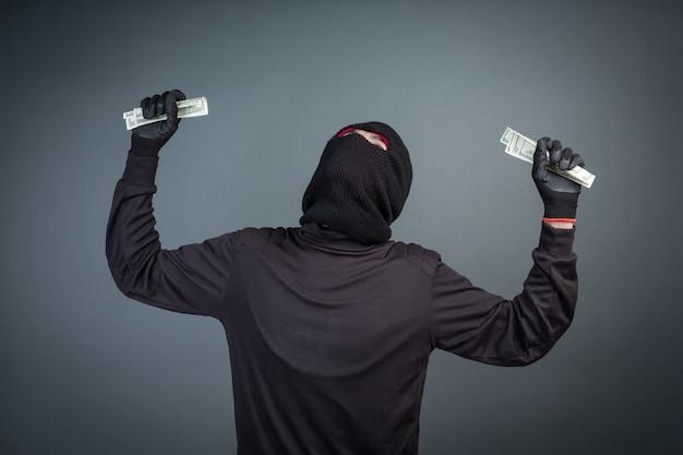 Kriminelle tragen schwarze masken, um dollarkarten auf grau zu halten