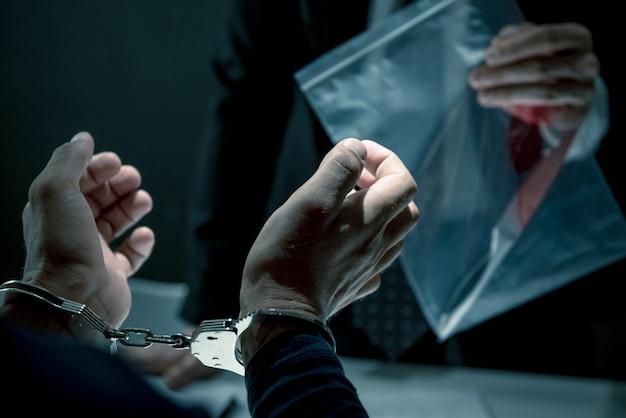 Krimineller mann mit den handschellen, die im befragungsraum interviewt werden
