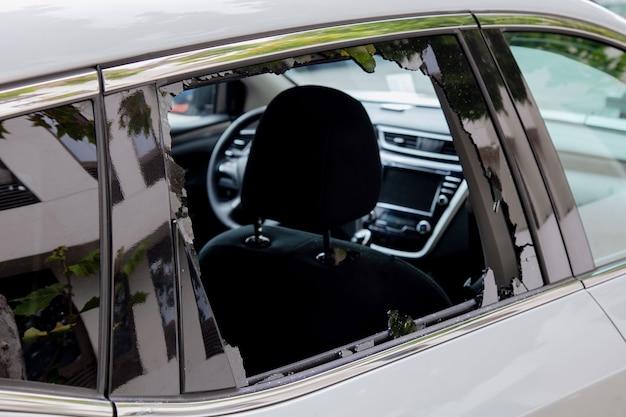 Krimineller vorfall hacken des autos zerbrochenes fenster eines autos zerbrochenes autofenster konzept der vandalismus-kriminalität und des diebstahls von persönlichen sachen aus dem auto