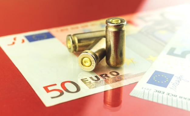 Kriminelles europa und blutiges schmutziges geldkonzept-fotohintergrund mit kugel- und euro-banknoten