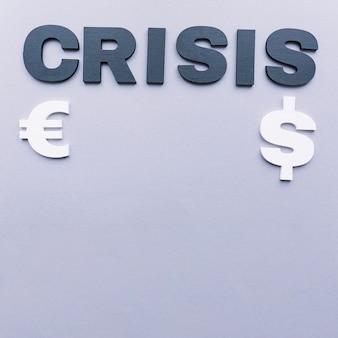 Krisenwort mit euro- und dollarsymbol auf grauem hintergrund