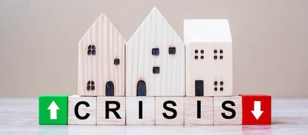 Krisenwürfelblöcke mit hölzernem hausmodell auf tabellenhintergrund.