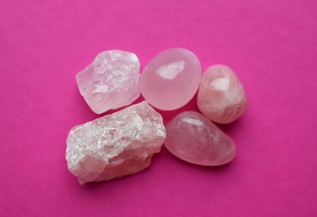 Kristalle aus rosenquarz auf einem leuchtend rosa hintergrund. schöne halbedelsteine