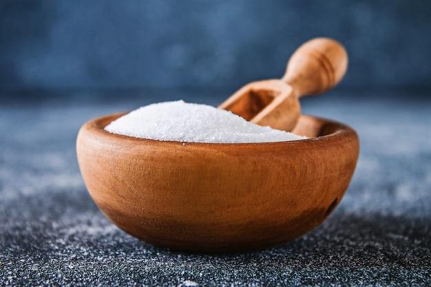 Kristalle des flachen salzes in einer hölzernen schüssel auf einer dunkelgrauen tabelle.