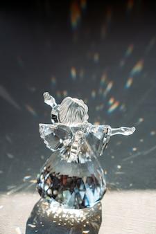 Kristallglas-engel in den strahlen der sonne mit reflektierendem, geprägtem funkeln-glaubens-hoffnungs-gnaden-konzept