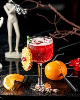 Kristallglas mit rotem cocktail, garniert mit orangefarbenem rad