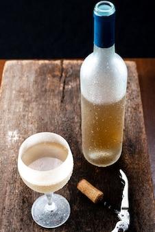 Kristallglas mit weißwein und einer flasche wein serviert sehr kalt über einem rustikalen holztisch