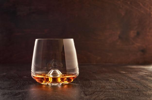 Kristallglas mit whisky auf einem holztisch Premium Fotos