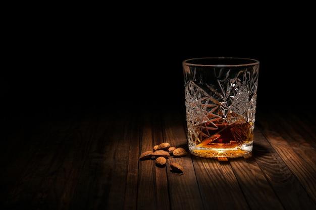 Kristallglas mit whisky und snäcken auf einem holztisch auf einem schwarzen hintergrund