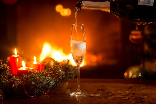 Kristallglas wird mit champagner gefüllt. brennender kamin und weihnachtsbaum im hintergrund