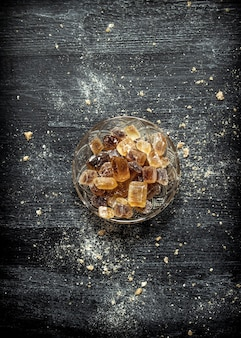 Kristalliner rohrzucker in einer untertasse auf schwarzem rustikalem tisch.