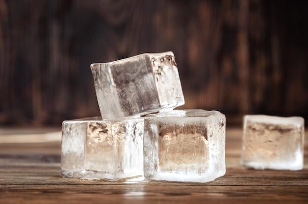 Kristallklare eiswürfel auf holz