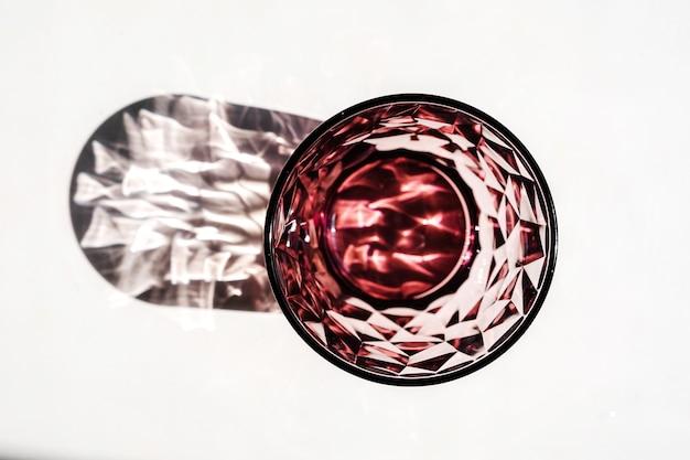 Kristallrotes glas auf weißem tisch. harte schatten im sonnenlicht.
