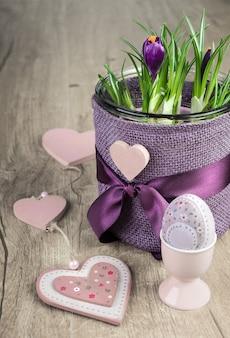 Krokusblumentopf und rosa osterdekorationen auf holz