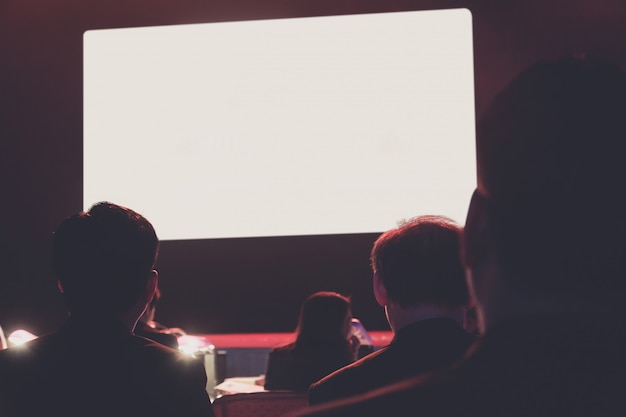 Krone betrachtet weißen monitor. publikum im konferenzsaal. geschäft und unternehmertum.