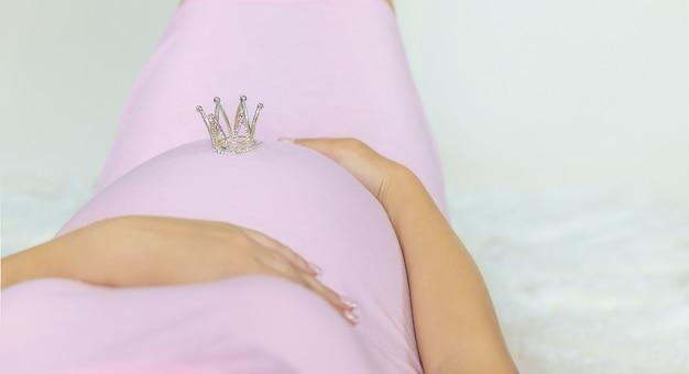 Krone der schwangeren frau auf dem bauch.