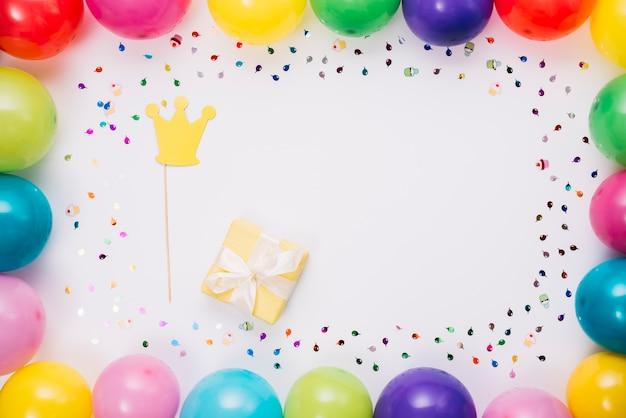 Kronenstütze und geschenkbox im bunten rahmen mit konfetti und luftballons