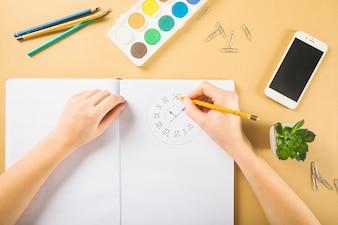 Kropfhände, die Uhr im Notizbuch zeichnen