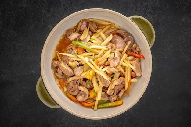 Kruang nai gai pad king, thailändisches essen, gebratene hühnernebenprodukte, verschiedene fleischsorten, zupf- oder organfleisch mit ingwer in keramikschale auf dunklem texturhintergrund, draufsicht