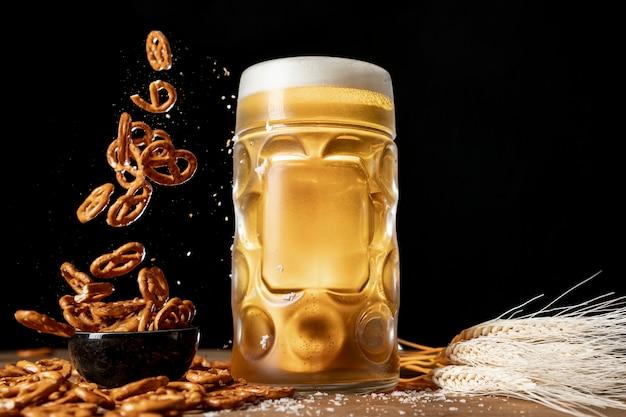 Krug bier mit fallenden brezeln auf einem tisch