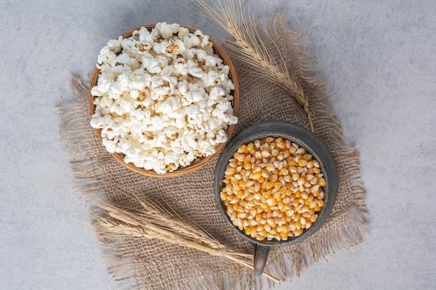 Krug gefüllt mit mais und schüssel gefüllt mit popcorn neben weizenhalmen auf einem stück stoff auf marmor.