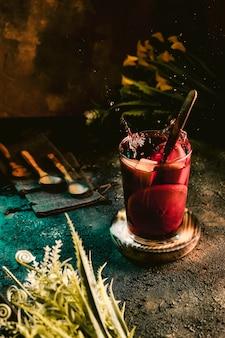 Krug kalte sangria mit früchten auf einer dunklen oberfläche
