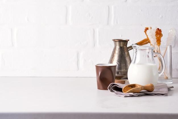 Krug milch und gemahlener kaffee für die zubereitung eines getränks zu hause auf einer steinarbeitsplatte gegen eine weiße küchenwand
