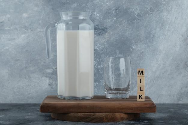Krug milch und glas wasser auf holzbrett.