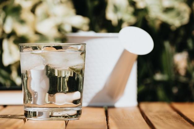 Krug und glas wasser auf einem holztisch an einem sonnigen sommertag