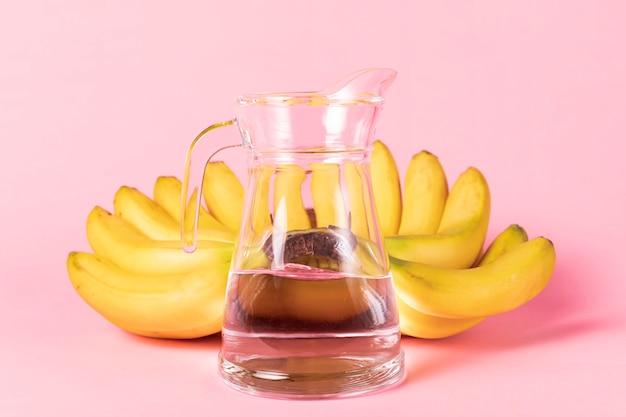 Krug wasser mit bananen im hintergrund