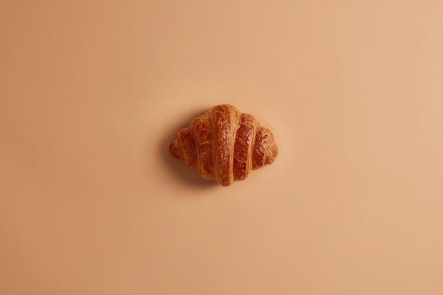 Krusten köstliches süßes buttercroissant zum frühstück auf braunem hintergrund. frisch gebackene süßwaren, leckeres dessert, junk food. hausgemachtes appetitliches backprodukt für naschkatzen. französisches essen