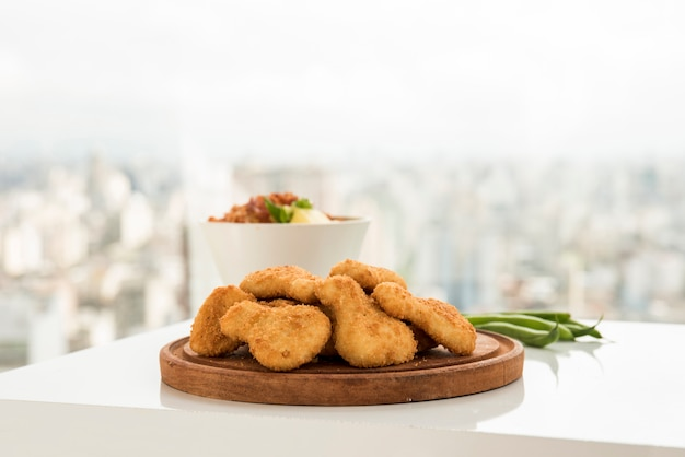 Krustige hühnernuggets gedient auf hölzerner platte