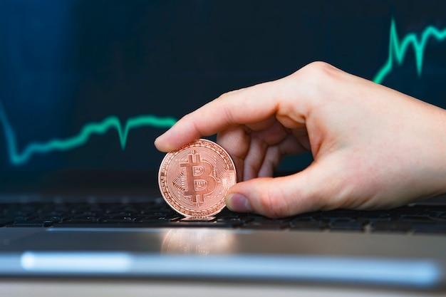 Kryptowährung bitcoin, goldmünze in der hand, vor dem hintergrund des wachstumsgraphen. wachstum von zitaten auf einem laptop. der hohe preis von btc.