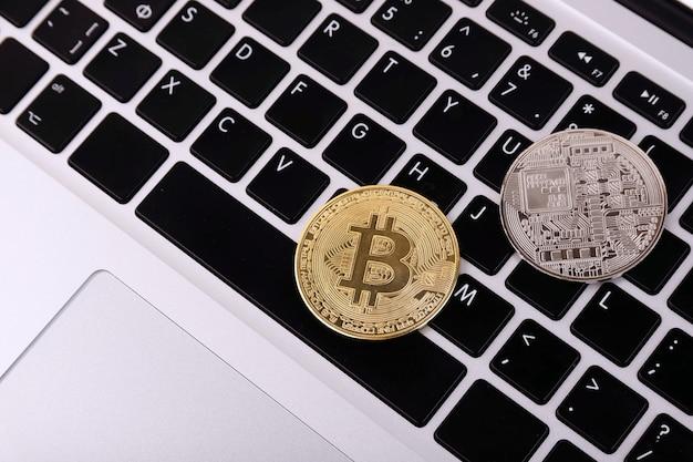 Kryptowährung und platin- und goldbitcoin auf der laptoptastatur. konzept.