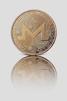 Kryptowährung von monero. goldmünze mit reflexion auf weißer glänzender oberfläche. konzeptionelles bild für weltweite kryptowährung und digitales zahlungssystem.
