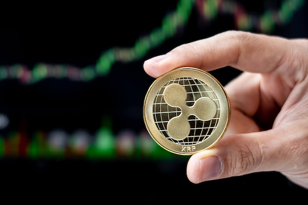 Kryptowährungsmünze golden ripple xrp mit kerzengraphhintergrund, krypto ist digitales geld