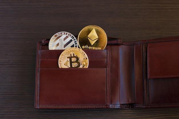Kryptowährungsmünze in der ledernen geldbörse auf breitem hölzernem hölzernem hintergrund