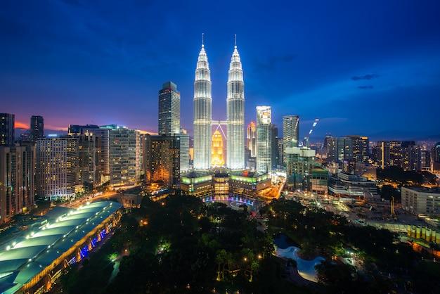 Kuala lumpur-stadtwolkenkratzer und grünfläche parken mit nettem himmelsonnenuntergang