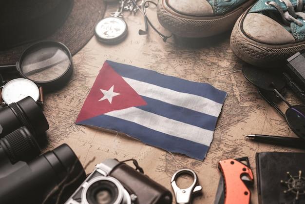 Kuba-flagge zwischen dem zubehör des reisenden auf alter weinlese-karte. touristisches bestimmungsort-konzept.