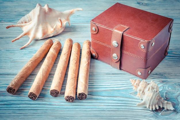 Kubanische zigarren, muscheln und eine kleine truhe auf einem blauen holztisch. erinnerungen an den urlaub