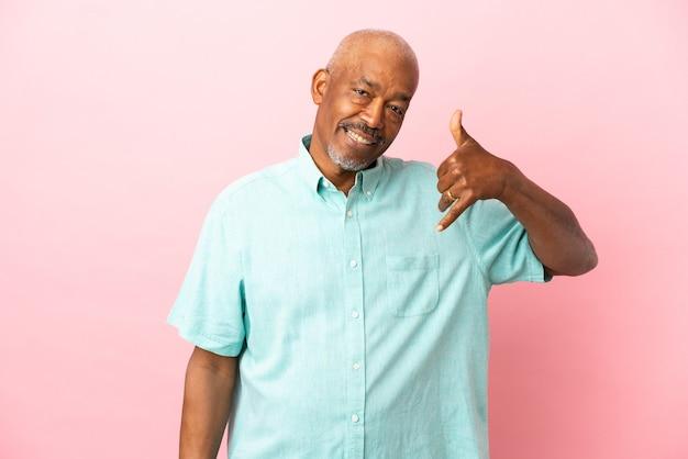 Kubanischer senior isoliert auf rosa hintergrund, der telefongeste macht. ruf mich zurück zeichen