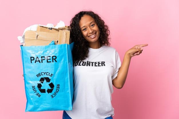 Kubanisches mädchen des teenagers, das eine recycling-tasche voll papier hält, um lokalisiert auf rosa hintergrund, der finger zur seite zeigt, zu recyceln