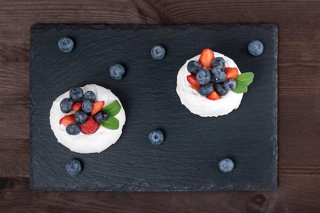 Kuchen anna pavlova. luftiges baiser, garniert mit frischen erdbeeren und blaubeeren.