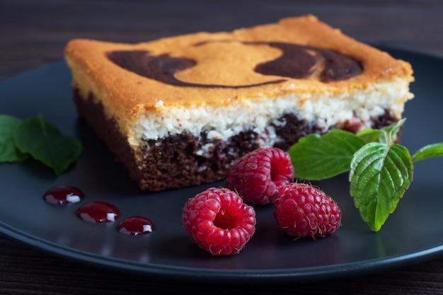 Kuchen auf einem teller mit schokoladen-brownies und quark-käsekuchen mit himbeeren.