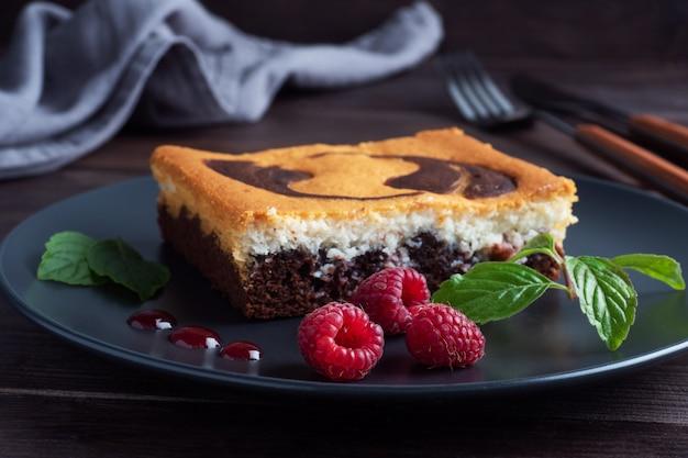 Kuchen auf einem teller mit schokoladen-brownies und quark-käsekuchen mit himbeeren