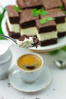 Kuchen auf einer gabel, kuchenstücke und kaffee mit milch
