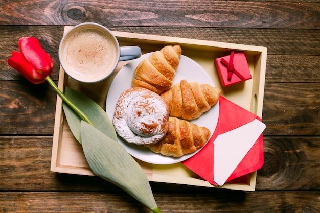 Kuchen auf platte in der nähe von blume, tasse getränk, brief und geschenkbox an bord